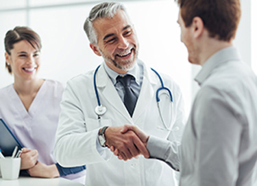doctor and nurse smiling and shaking hands with man