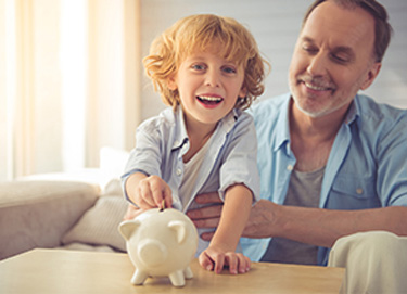 kid putting money in piggy bank with man smiling beside kid