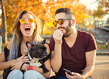 man and woman laughing with dog in lap